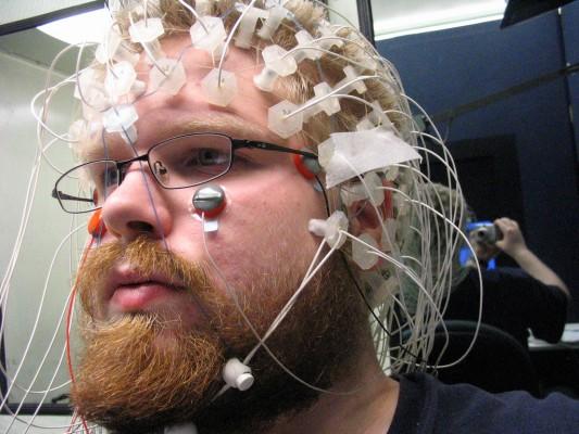 Homme avec la tête bardée de capteurs, lors d'une expérience