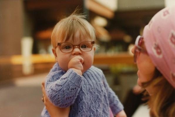 Bébé dans les bras de sa mère portant une paire de lunettes