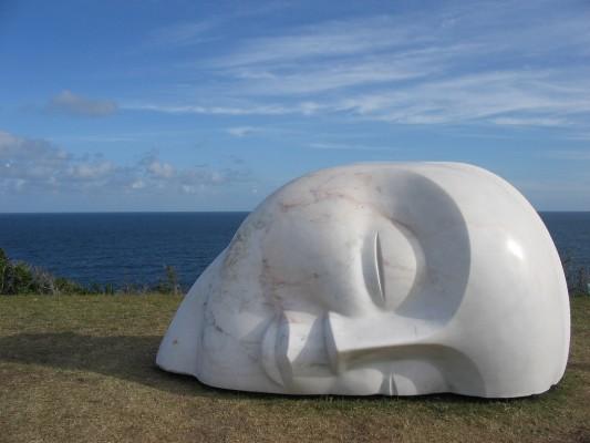 Statue représentant un demi visage couché, en paix