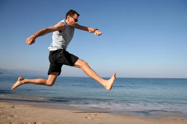 Homme courant sur une plage