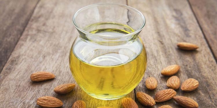 Vase contenant de l'huile d'amande douce avec des amandes