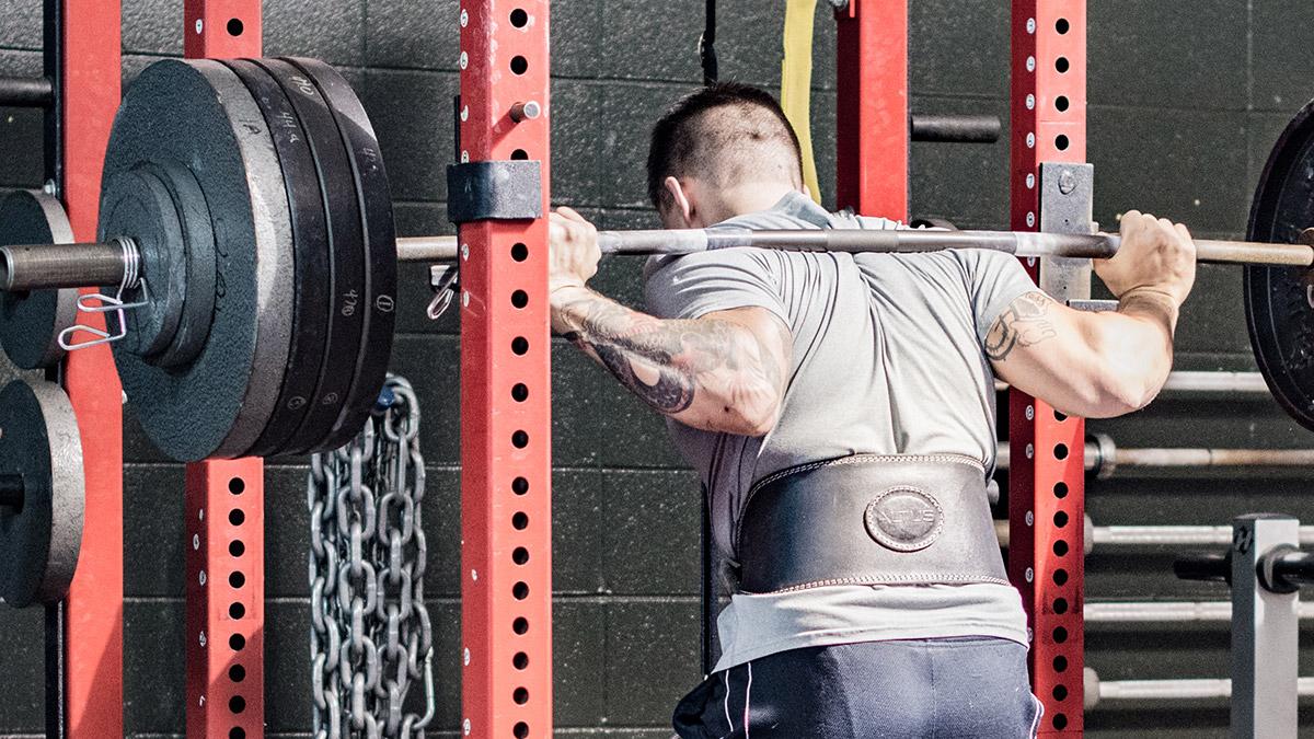 Sportif, de dos, faisant des squats avec une charge lourde