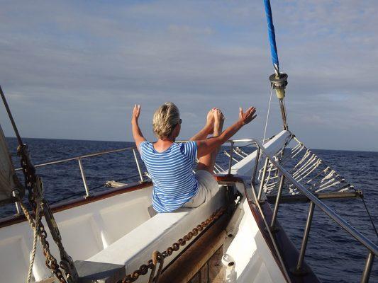 Femme faisant une extension pilates sur l'avant d'un voilier