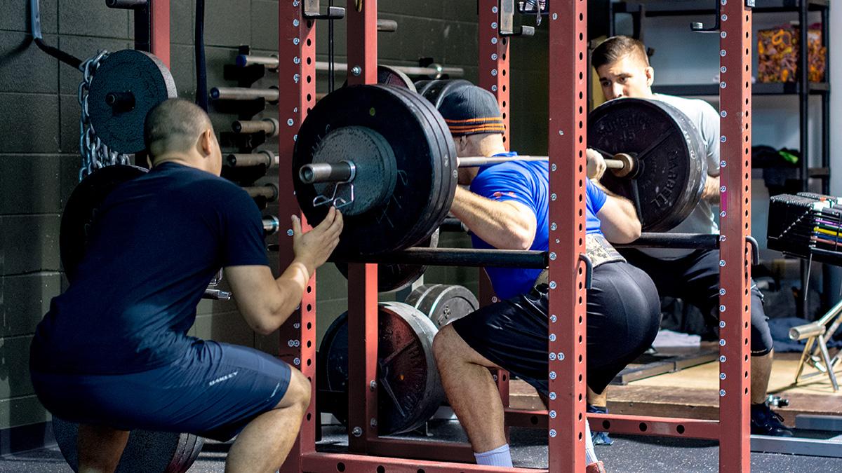 Squat avec des poids lourds, vu par l'arrière