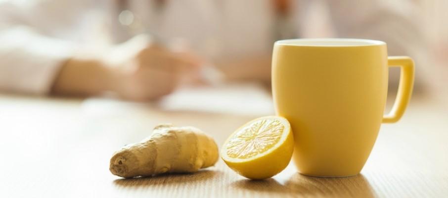 Tasse de tisane avec un morceau de citron et une racine de gingembre