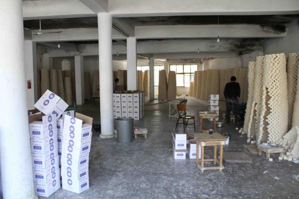 """Une vue générale de """"l'usine"""", avec les emballages blancs et bleus et les piles de savon blancs en train de sécher."""