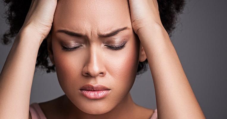 Une femme fronce les sourcils et ferme les yeux de douleur