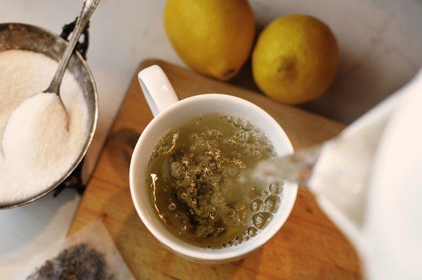 Vue du dessus d'une tasse où on verse du thé clair